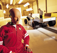 A test dummy is shown waiting to be placed in a race car for crash testing at CAPE.