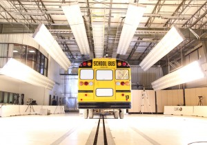 A school bus sits on CAPE's barrier block test track surrounded by lights.