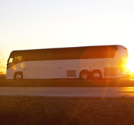 A motorcoach heads down the highway at sunset.