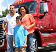 A trucker and his family pose before his truck.
