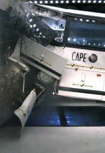 A motorcoach is shown crashing into CAPE's barrier block during a test.