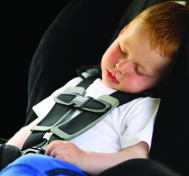 Photo of child asleep in car seat.